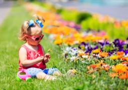 enfant dans l'herbe jouant avec les fleurs
