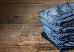 5 jeans pliés sur une table en bois