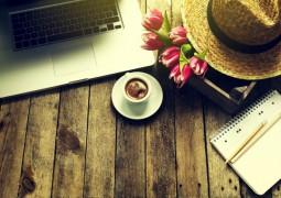table en bois avec un ordinateur un chapeau des fleurs un carnet avec des crayons à papier et un café