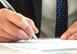 homme crayon à la main écrivant sr un papier