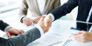 poignée de main entre deux hommes en costard dans un bureau au dessus d'une bureau avec un contrat