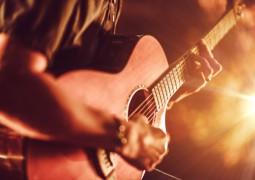 guitare acoustique tenus par un homme en jouant avec une lumière vive sur la droite