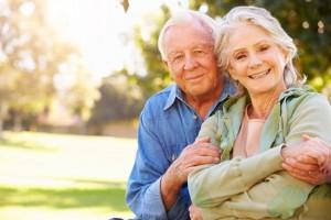 un couple de retraitée se tenant dans les bras le regard tourné vers l'objectif.