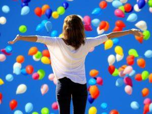 Montage photo d'une femme de dos avec les bras tendus sur les côtés avec un fond avec des ballons de baudruche.