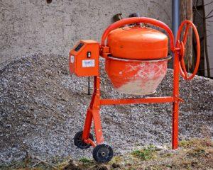 Voici une image d'une bétonnière de couleur orange d=sur un chantier